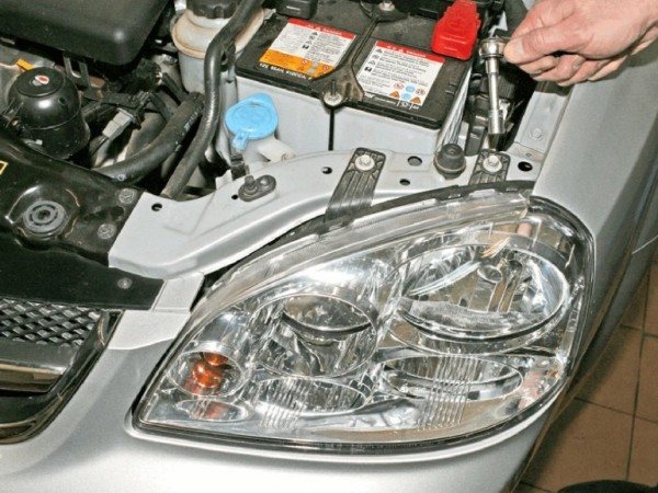 На фото - замена лампы ближнего света на Шевроле Лачетти седан невозможна без снятия блок-фары